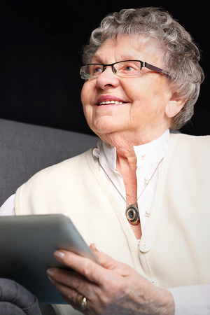 Elderly woman surfs the internet. Stock Photo