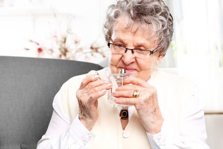 eau de perfume: Mature well groomed woman with perfume bottle, smelling perfume. Stock Photo