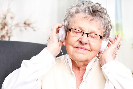 listening to music: La abuela escucha música. Foto de archivo