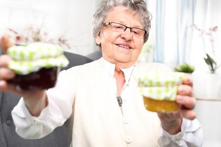 personally: Mature woman with personally prepared jars of jams. Stock Photo