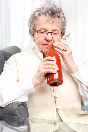 the great grandmother: Grandmas preserves, puree with red tomatoes. An elderly woman with a bottle personally prepared processed tomato products