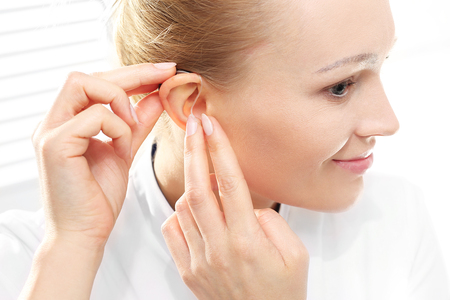 Young woman assumes a hearing aid