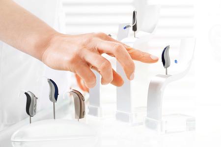 Hörhilfen. Man zeigt mit dem Finger auf einem Modell Hörgerät Standard-Bild - 60680635