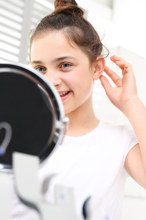 hearing aid: Cheerful girl assumes hearing aid viewing in the mirror