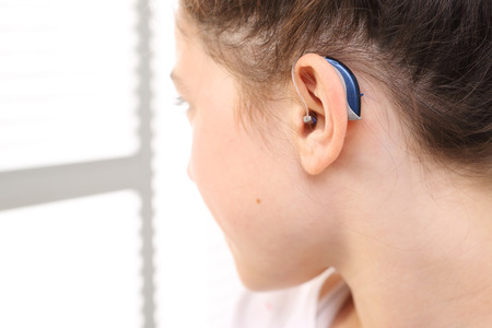 A child with a hearing aid.