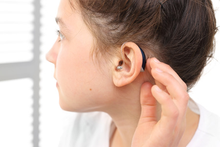 The girl assumes hearing aid. Stockfoto