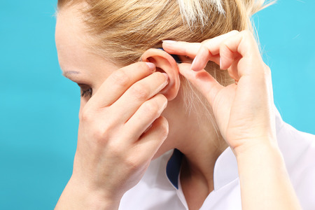 Hearing aid. The doctor assumes the woman hearing aid in your ear Stock Photo