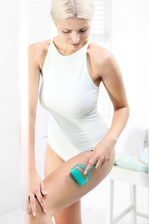 massager: Anti-cellulite massage. Woman massaging thigh massager standing in the shower Stock Photo
