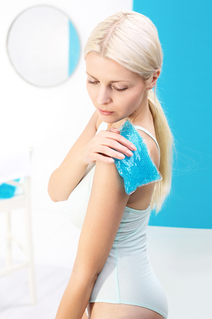 puts: Injury. The woman puts the gel pack to the shoulder Stock Photo