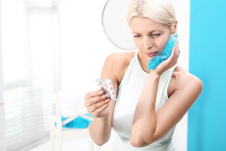 De vrouw zet een koud kompres nuttig voor kiespijn. Stockfoto