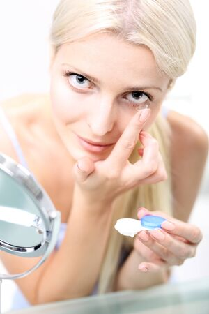 lentes de contacto: Contact lenses. woman assumes contact lenses. Foto de archivo