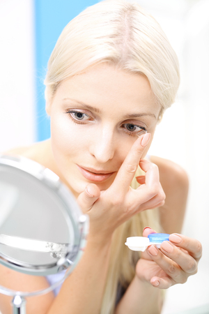 lentes de contacto: Inserting contact lenses. The woman assumes contact lenses.