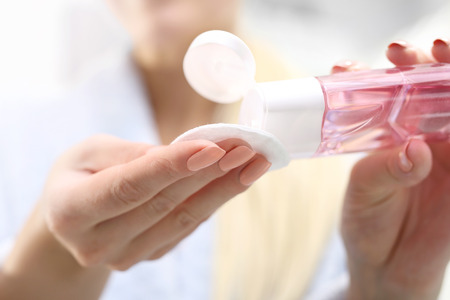Make-up removal. The woman pours a tonic on a cotton pad.