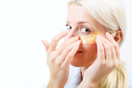 beauty and health: Gold pads, reduction of wrinkles. Portrait of a beautiful young woman with collagen mask around the eye