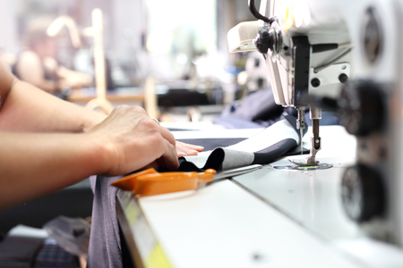 The woman sewing on the machine. The production plant, sewing clothes by seamstresses on the sewing machine Stock Photo