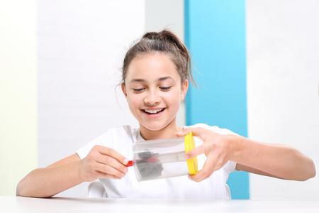 Ein Magnetfeld. Das Kind sieht das Phänomen des Magnetfeldes auf die Lehren der Physik.