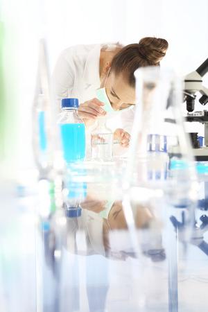 analytical chemistry: Chemist examine the samples under a microscope.