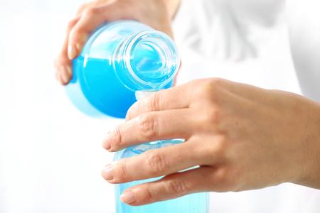 bureta: Experiencia química. El químico vierte líquidos en los gobernantes de cristal Foto de archivo