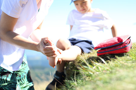 An accident on a mountain trail. The child twisted his ankle during a mountain tour. Wound broken leg. Standard-Bild