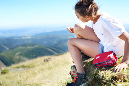 관광객은 산길의 경사면에 앉아 무릎 부상을 치료합니다.