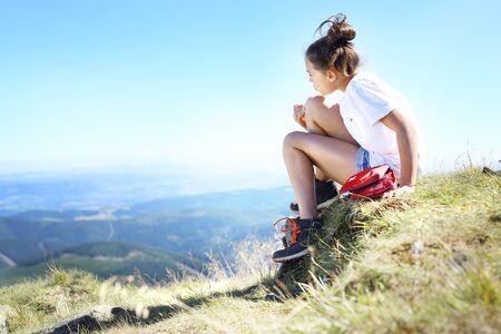 niños vistiendose: Turista desinfecta la herida en la rodilla mientras está sentado en la ladera de un sendero de montaña.