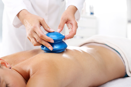 cupping therapy: Masseur massaging her back rubber Chinese bubble. Stock Photo