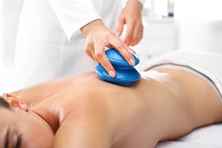 Chinese cupping massage. Masseur massaging her back rubber Chinese bubble.