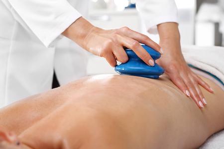 Back massage Chinese bubble. Masseur massaging her back rubber Chinese bubble.