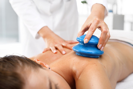 cupping therapy: Massage therapy, massage Chinese cupping. Masseur massaging her back rubber Chinese bubble. Stock Photo