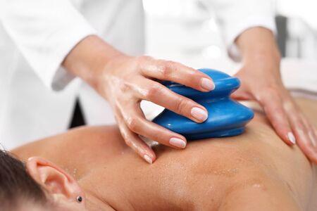 Wellness and spa. Massage. Masseur massaging her back rubber Chinese bubble. Stock Photo