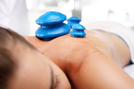 cupping therapy: Back massage. Masseur massaging her back rubber Chinese bubble.