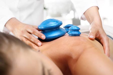 Alternative medicine. Massage. Masseur massaging her back rubber Chinese bubble.