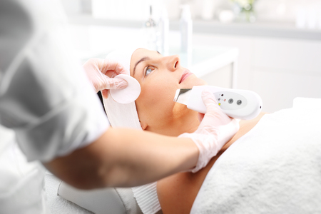 Cavitation peeling, beauty treatment on face. The woman's face during a facial at a beauty salon