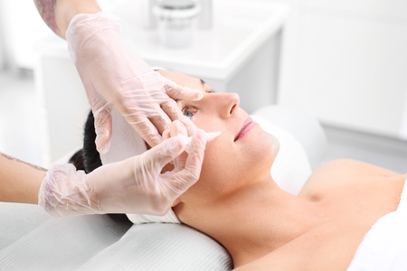 revitalization: Mesotherapy needle, beautician punctures womans face. Face lift, needle mesotherapy