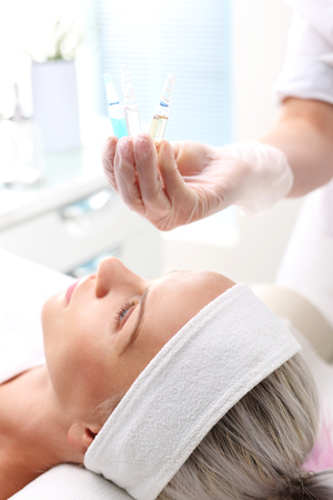 ampoule: Cosmetic ampoule, serum applied to the face of a woman. Stock Photo