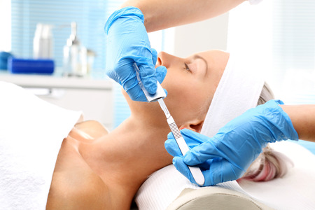 Dermabrasion manual using a surgical blade. White woman during surgery using a scalpel.