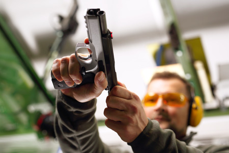 Shooting a gun at a shooting range. The man at the pistol shooting reloads