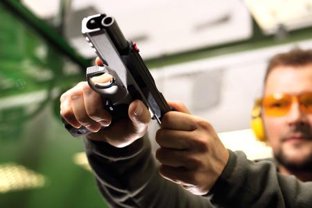 Schietbaan. De man bij het pistool schiet opnieuw Stockfoto