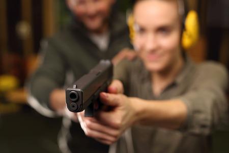 mujer con pistola: La mujer que apunta un arma a un blanco Foto de archivo