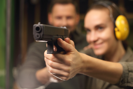 pistolas: Mujer dispara un arma de fuego en un campo de tiro.