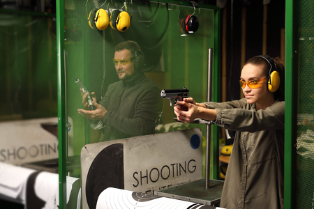 Vrouw schiet een pistool op een schietbaan.