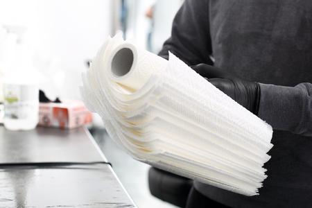A tattoo artist preparing disposable paper towels.