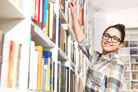 The girl in the bookstore chooses the book Stock Photo