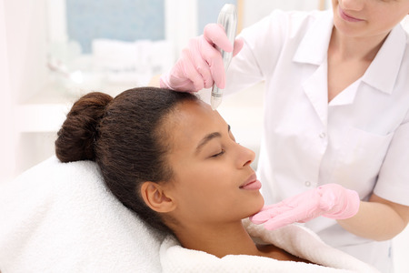 Beautician performs a needle mesotherapy treatment on a womans face Zdjęcie Seryjne