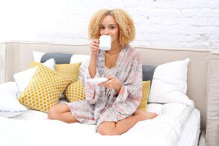 mujer en la cama: Cafe mañanero. café de la mañana consumición de la mujer joven en la cama Foto de archivo