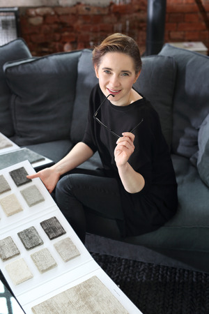 interior decorating: Interior decorating, shopping carpet. Woman chooses carpet for the living room