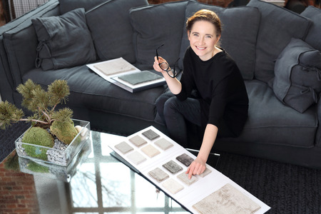 Interieur ontwerper met de sonde tapijten. De vrouw kiest tapijt voor de woonkamer Stockfoto - 70897943
