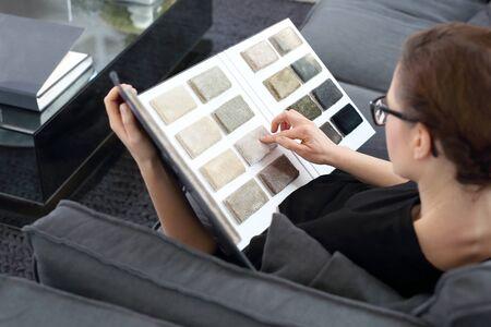 De vrouw kiest tapijt Stockfoto