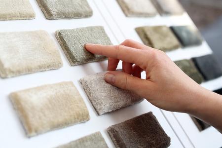 Picker carpet. Woman in shop with carpets chooses carpet probe