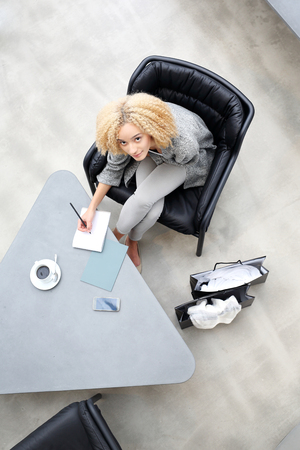Shopping. Girl taking notes while sitting on the desk Stock Photo